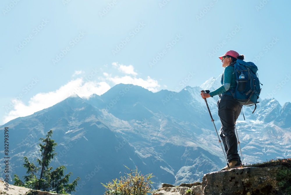 Fototapety, obrazy: Young hiker backpacker female using trekking poles enjoying mountain view during high altitude Acclimatization walk. Everest Base Camp trekking route, Nepal. Active vacations concept image