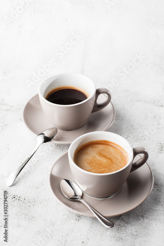 Fototapeta Two white cups of hot black coffee with milk isolated on bright marble background. Overhead view, copy space. Advertising for cafe menu. Coffee shop menu. Vertical photo. obraz