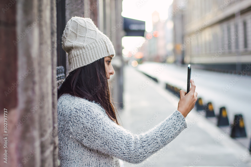 Fototapety, obrazy: Young woman taking a selfie or a photography using her cellphone smart phone in the street