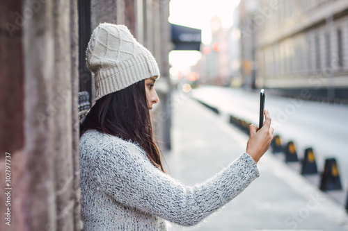 Young woman taking a selfie or a photography using her cellphone smart phone in Fototapete