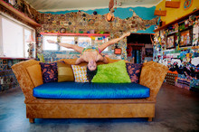 Fun And Funky Hispanic Woman Doing Splits On The Couch In A Funky House.