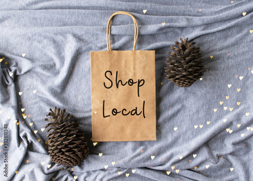 "Fotomural  ""Shop Local"" text on a plain brown paper bag flat lay with pine cones and hearts"