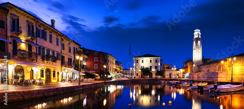 Obraz Boats in old town port of Lazise at twilight. The town is a popular holiday destination in Garda Lake district. - fototapety do salonu