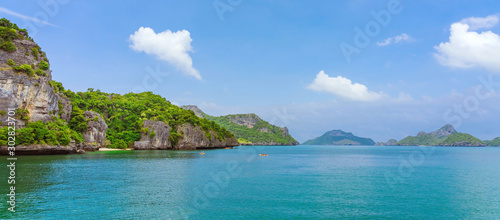 Fototapety, obrazy: Tourist kayaking in blue Idyllic turquoise ocean to explore near the island with lush green jungle trees and lime stone mountains at Ang Thong National Marine Park, Thailand.