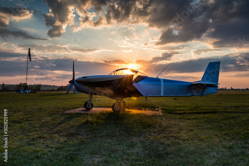 A small sports aircraft parked at the airfield at picturesque sunset Wallpaper Mural