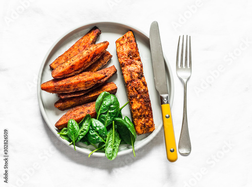 Fototapeta Crispy spice crust baked salmon with sweet potato and spinach - healthy balanced lunch on light background, top view obraz