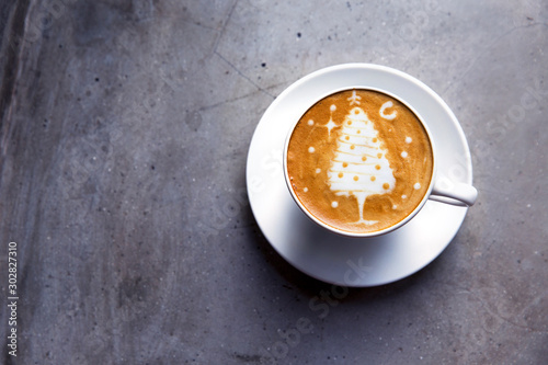 Tasty cappuccino with Christmas tree latte art on grey concrete background.