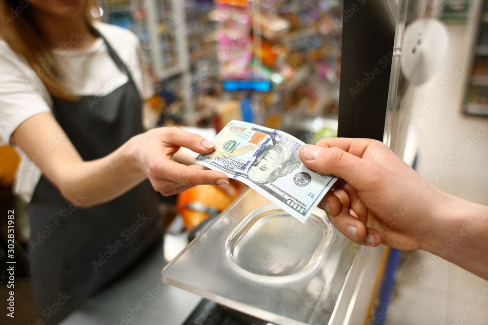 Fototapeta Young man paying for goods in supermarket, closeup