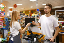 Young Man Paying For Goods In Supermarket