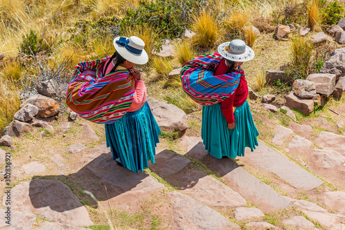 Photo Two Quechua indigenous women in traditional clothing and textile walking down the steps on Taquile island by the Titicaca Lake, Puno, Peru