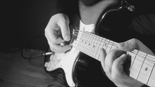 Musician Plays Guitar At Studio . Black And White