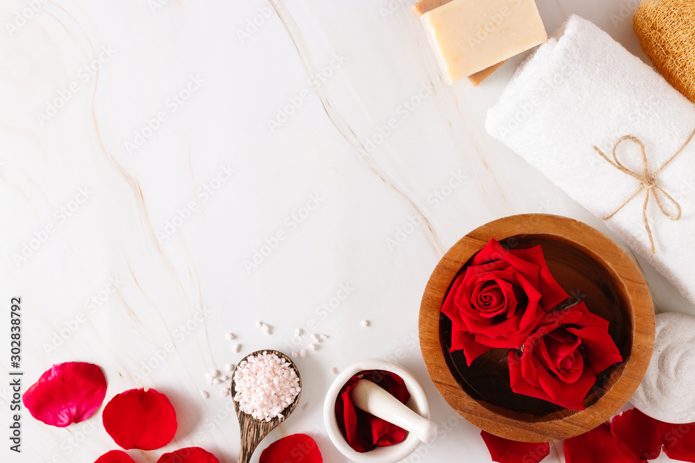Fototapeta Spa bath product with rose oil and.Rose petals on a white background.