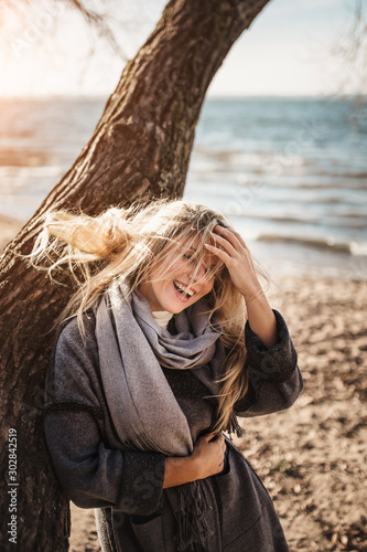 Photo Happy cheerful blonde by the sea fun catches her hair from a strong wind