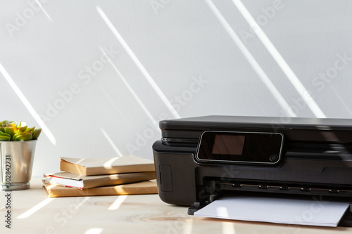 Fotomural  Front view of a black printer machine on a table