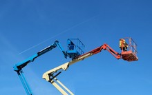 Two  Aerial Work Platforms Of Cherry Picker Against Blue Sky