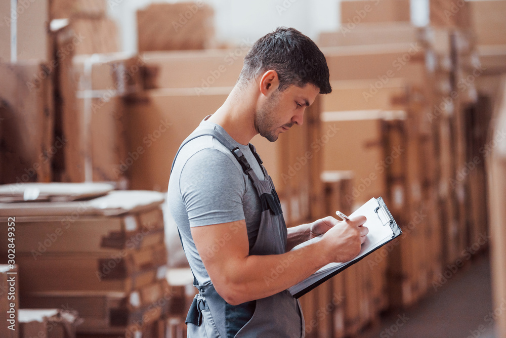 Fototapeta Storage worker in uniform and notepad in hands checks production