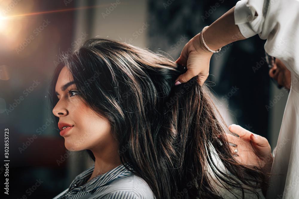 Fototapeta Hairstylist Fixing Woman's Hair