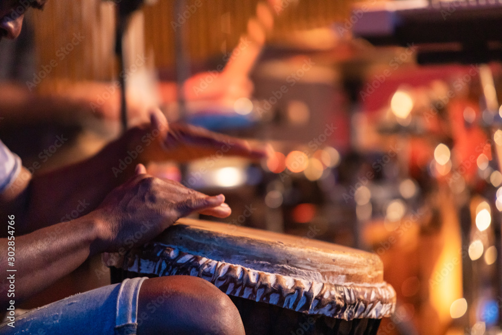 Fototapety, obrazy: Close-up of man's hands playing on African djembe drum, selective focus on hands with blurry background during a traditional music performance