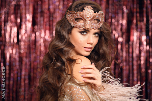 Obraz Christmas holiday party. Beautiful brunette with Healthy wavy hair. Fashion Beauty Girl with carnival mask Isolated on golden bokeh lights Background. Glamour Makeup. Jewelry copy space. Hairstyle. - fototapety do salonu