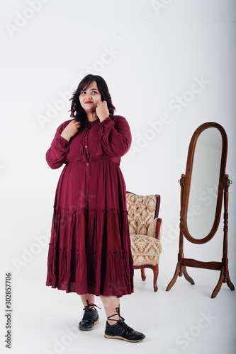 Fotografía  Attractive south asian woman in deep red gown dress posed at studio on white background against mirror and chair