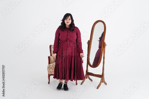 Pinturas sobre lienzo  Attractive south asian woman in deep red gown dress posed at studio on white background against mirror and chair