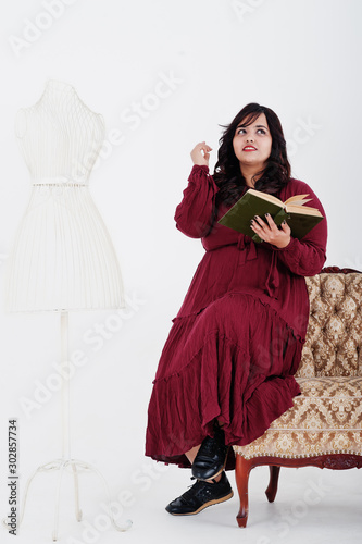 Fotografía  Attractive south asian woman in deep red gown dress posed at studio on white background against mirror and chair, read a book