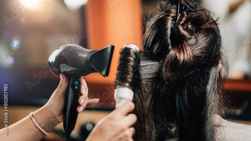 Photo Hairdresser Curling Woman's Hair