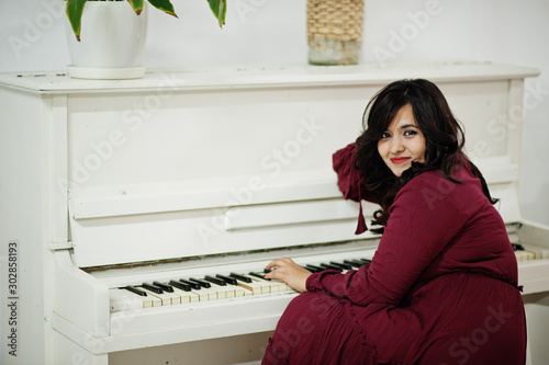 Fotografía Attractive south asian woman in deep red gown dress posed at room and play on piano