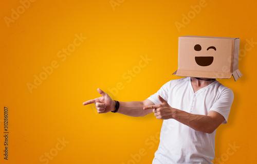 Fotografía  Funny man wearing cardboard box on his head with smiley face