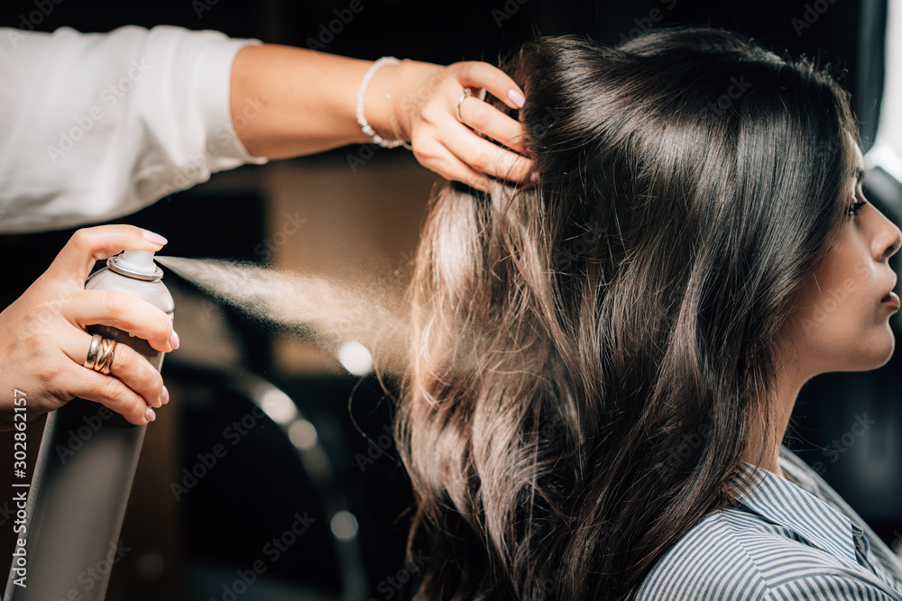Fototapeta Hairstylist Spraying Woman's Hair