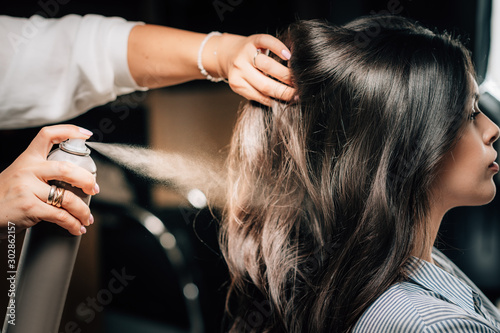 Hairstylist Spraying Woman's Hair