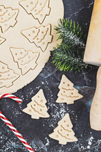 Overhead Flat Lay Concept For Baking Christmas Cookies With Rolled Out Cookie Dough, Cookies In The Shape Of Christmas Trees, Candy Canes And Fir Branches On Marbel Background