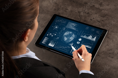 Business woman verifying reports on tablet with pencil in business suit Fototapeta