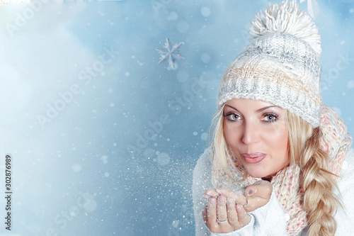 Fotografia  Portrait of a young blonde with light eyes in a winter hat and scarf blowing flickering snow from her hand