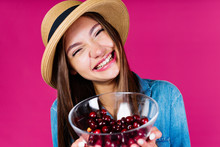 The Girl With A Vase Filled With Cherries, Smiling, Narrowed Her Eyes And Tilted Her Head To The Side, Seeking Approval And Support, Embarrassed. Background Pink