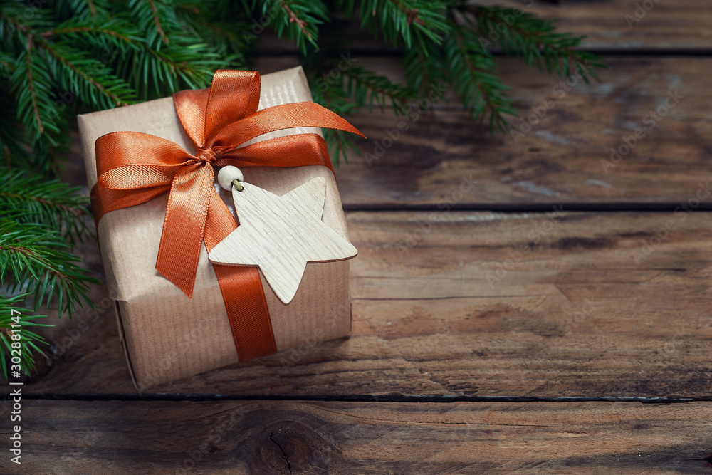 Fototapeta Christmas decorations. Gift wrapped craft with fir branches and holiday decoration on wooden background.