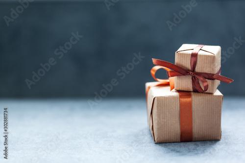 Fotografija Holidays present boxes with brown ribbon on dark background