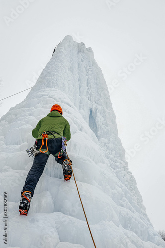 Photo Alpinist man with ice tools axe in orange helmet climbing a lar