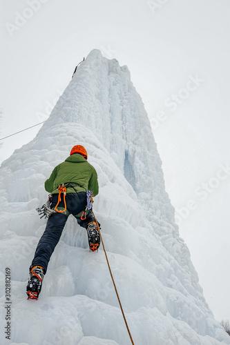 Alpinist man with ice tools axe in orange helmet climbing a lar Wallpaper Mural