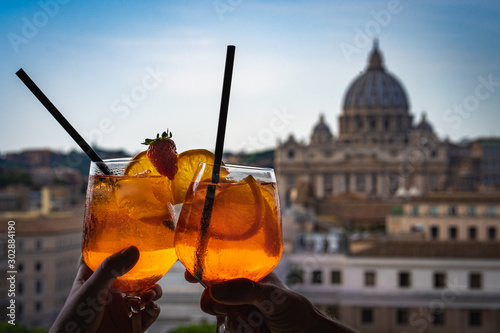 A couple is holding glasses of Aperol in the bar inside the Castle Sant'Angelo Fototapeta