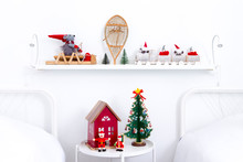 Small Round Table And Shelf Decorated For The Holidays With Small Red House And Christmas Tree, Wooden Toys And Train, Plush Mouse On Sled And Antique Snow Shoe In White Twin Bedroom