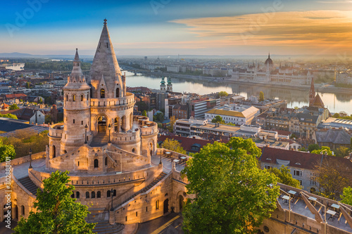 Budapest, Hungary - Beautiful golden summer sunrise with the tower of Fisherman's Bastion and green trees. Parliament of Hungary and River Danube at background. Blue sky. #302888101