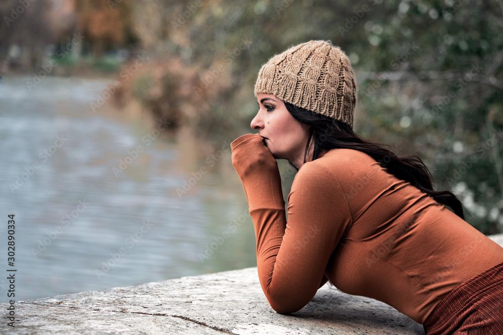 Fototapeta sad woman looking towards a lake