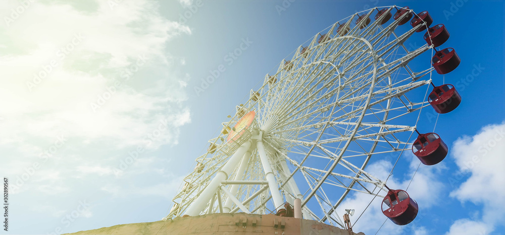 Fototapety, obrazy: Very large ferris wheel located on a high rise building, the baskets to carry passenger in dark red. In the daytime, the sky is bright, with cloud. Warm tone like a fairy tale.Taken in Okinawa, Japan