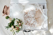 canvas print picture - Luxury wedding dress in white box, beige women's shoes and bridal bouquet on bed, copy space. Bridal morning preparations. Wedding concept