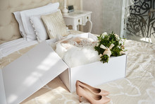 Luxury Wedding Dress In White Box, Beige Women's Shoes And Bridal Bouquet On Bed In Hotel Room, Copy Space. Bridal Morning Preparations. Wedding Concept