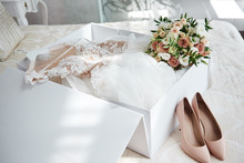 Luxury Wedding Dress In White Box, Beige Women's Shoes And Bridal Bouquet On Bed, Copy Space. Bridal Morning Preparations. Wedding Concept