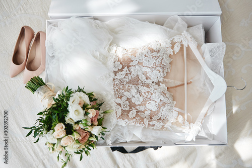 Foto Luxury wedding dress in white box, beige women's shoes and bridal bouquet on bed, copy space