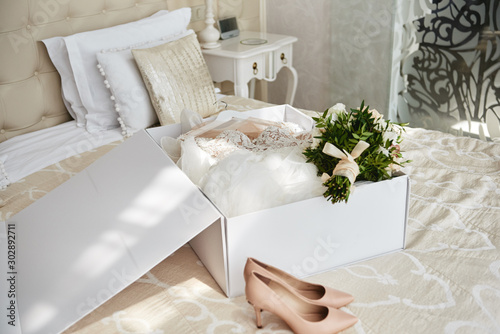Luxury wedding dress in white box, beige women's shoes and bridal bouquet on bed in hotel room, copy space Fototapete