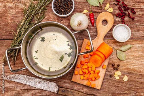 Obraz Transparent duck broth in pan with fresh ingredients. Traditional bouillon for healthy dishes. Spices, vegetables, old wooden table - fototapety do salonu